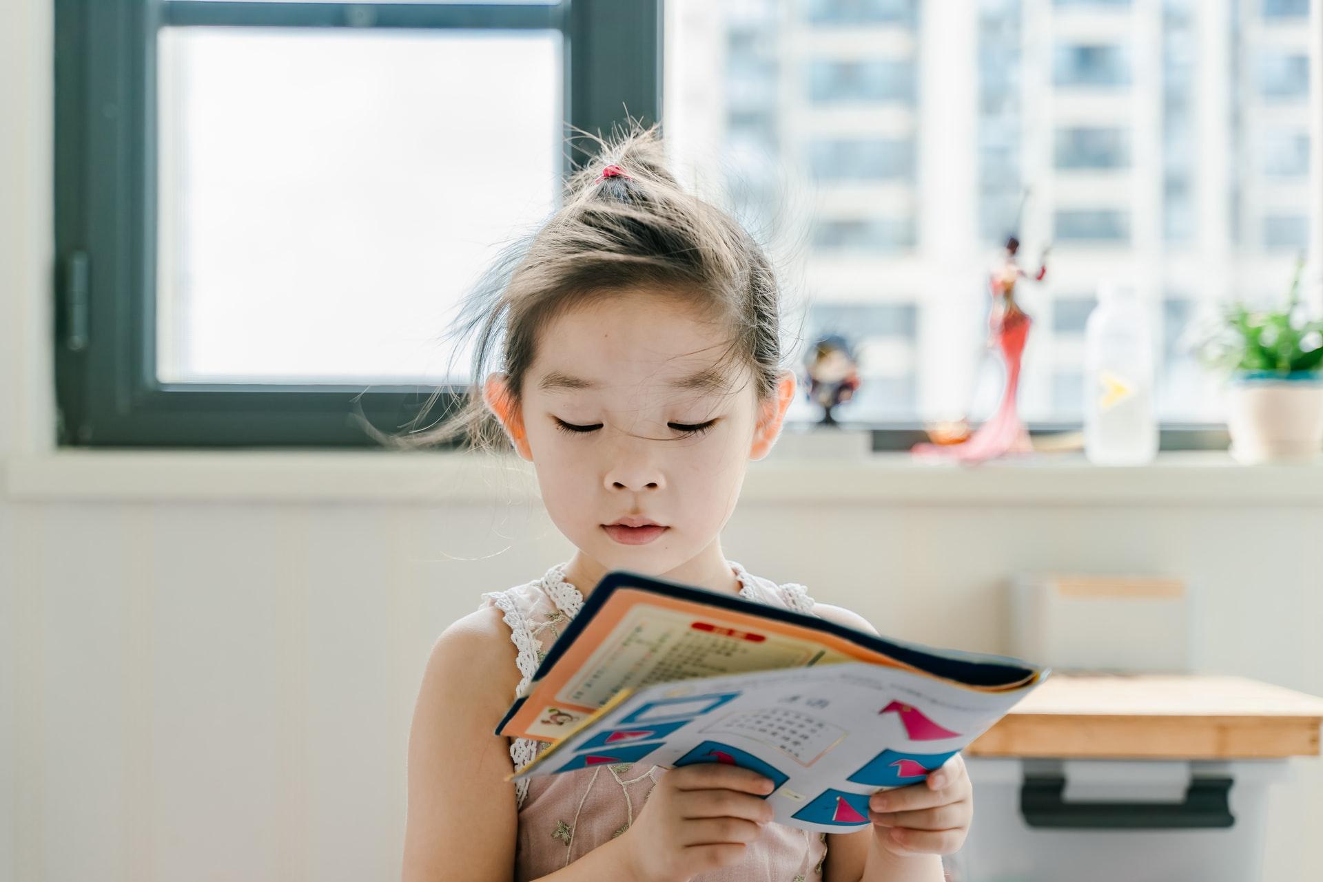 窓辺で読書をする小さな女の子