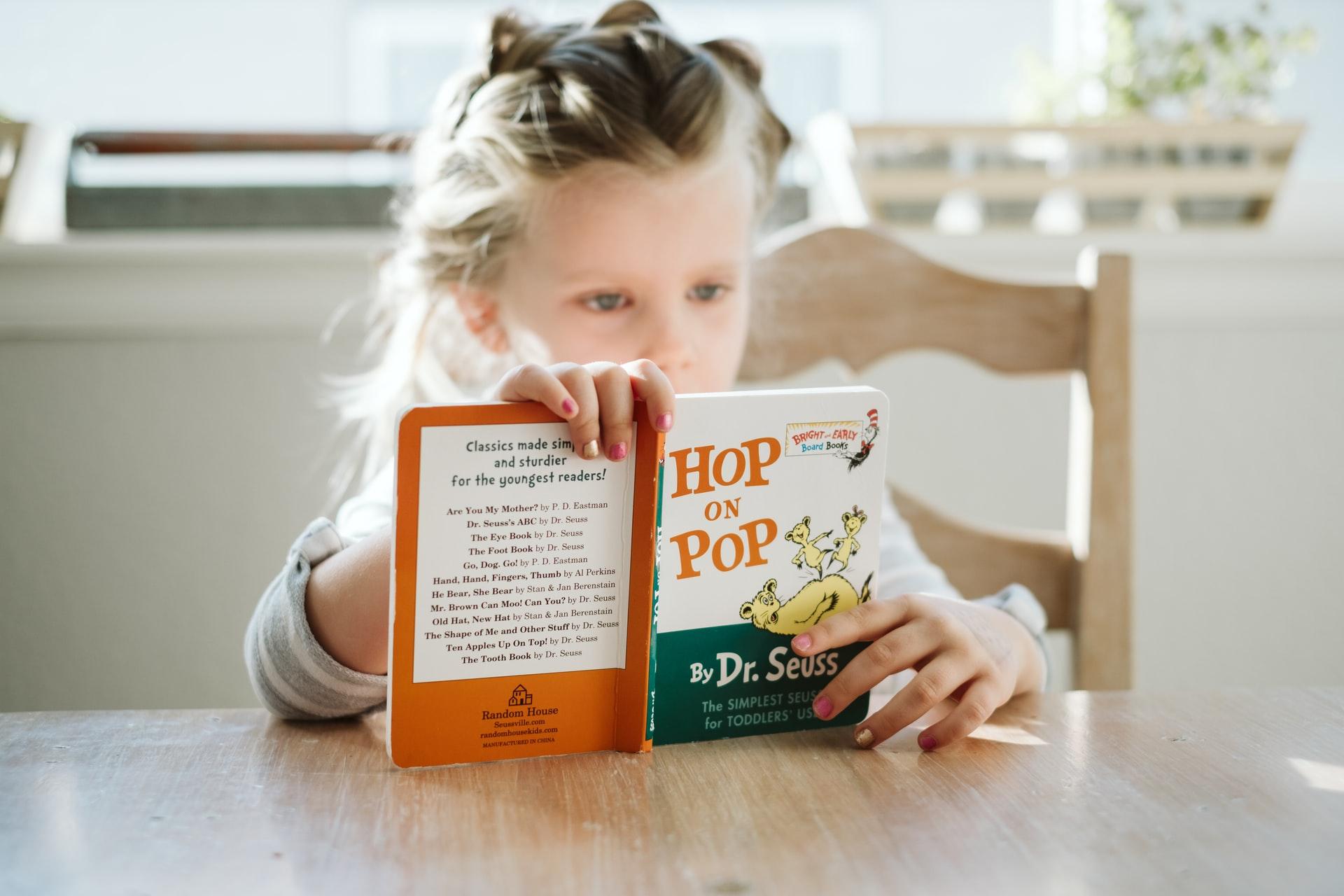 椅子に座って英語の本を読む女の子