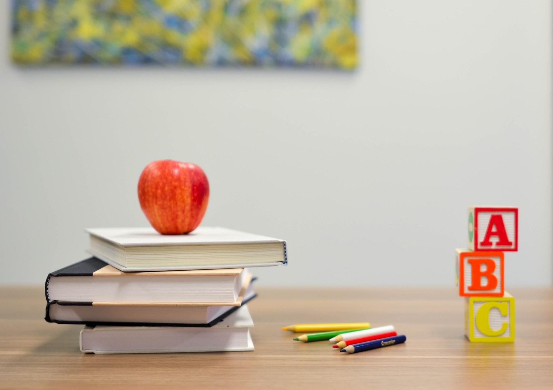 机の上に積まれた本の上に、置かれたリンゴ